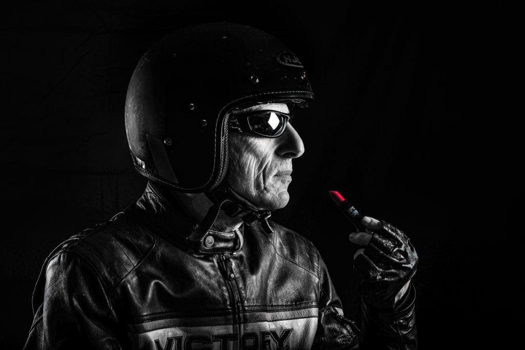 Portrait atypique noir et blanc d'un motard avec un bâton de rouge à lèvre